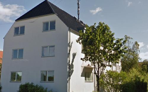 Andelsforeningen Vigerslevvej 235 med et træ i forgrunden set fra gaden